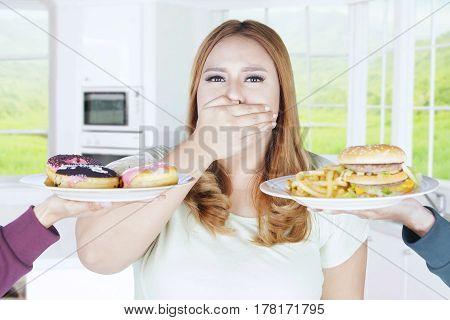 Portrait of overweight woman closed her mouth with hand while refuses high calorie food