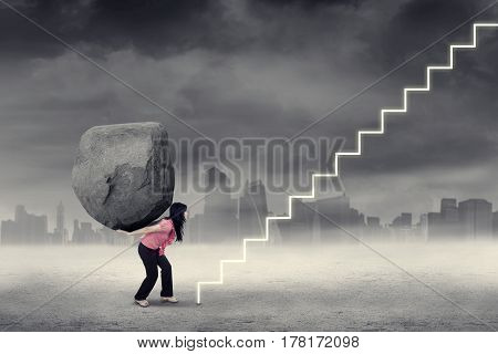 Picture of a strong businesswoman bringing a boulder on her back and climbing a stairway. Concept of hard work and difficult road