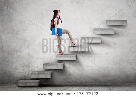 Female college student walking upward on the stairs while carrying a backpack and folder