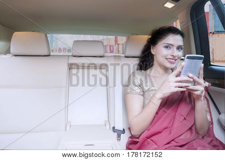 Picture of a successful Indian female importer sitting in the car while using mobile phone and wearing saree clothes with container on the background