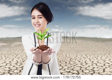 Beautiful young woman smiling at the camera while holding a plant on her hand at the drought land