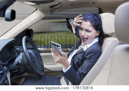 Indian businesswoman driving a car while playing a mobile phone and looks protecting her face before car accident on the road