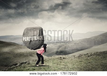 Female worker walking on the mountain while bringing a boulder with a Persistence word on her back. Concept of worker persistence