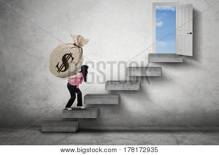 Female worker walking on the stairs while carrying a sack of dollar currency toward a door