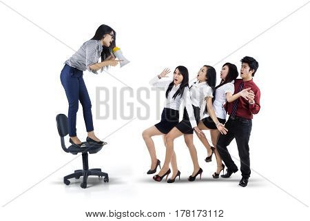 Picture of young leader screaming to her teamwork by using a megaphone isolated on white background