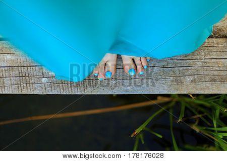 Girl in a blue dress on a bridge near the lake