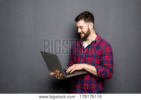 Handsome Casual Man Showing Blank Laptop Screen Over Gray Background.
