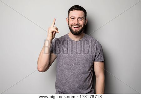 Young Smiling Man Having A Good Idea Isolated On White. Copy Space And T Shirt. Finger Up. Selective