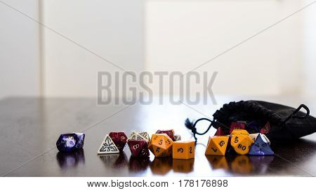 Colorful roleplaying dice scattered on a table with reflection