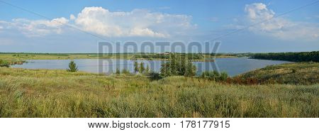 Panoramic view of the rural landscape. Blooming meadow and tortuous river in the late afternoon.