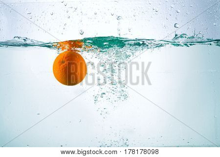 Orange in a stream of water on a white background, studio light