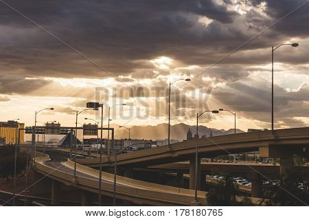 Sunlight beaming through dark clouds over the desert in Las Vegas, Nevada. Freeway overpass city buildings and distant mountains on a beautiful stormy day.