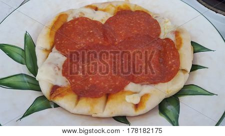 Home-made pizza with salami and cheese as topings