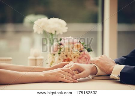 The bride and groom are sitting at the table holding hands against the background of beautiful flowers