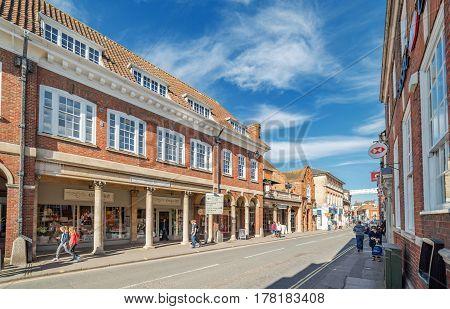 Farnham, UK. 25th March 2017. Pedestrians are walking along The Borough in Farnham on a sunny spring day.