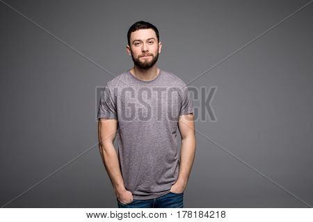 Handsome Young Man,boy,posing In Grey Shirt And Jeans With Hands In Pockets On Grey
