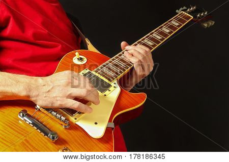 Hands of guitarist playing the guitar on a dark background