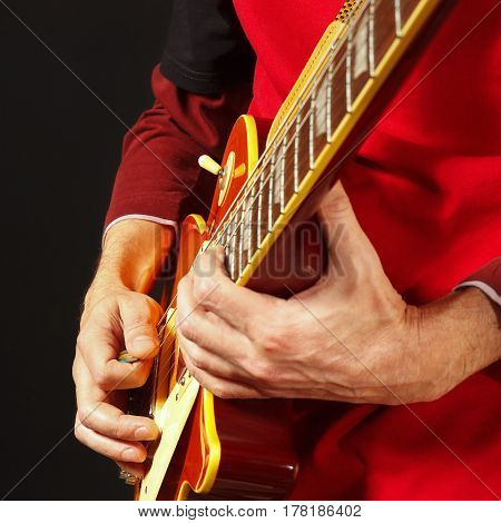 Hands of musician playing the guitar on a dark background