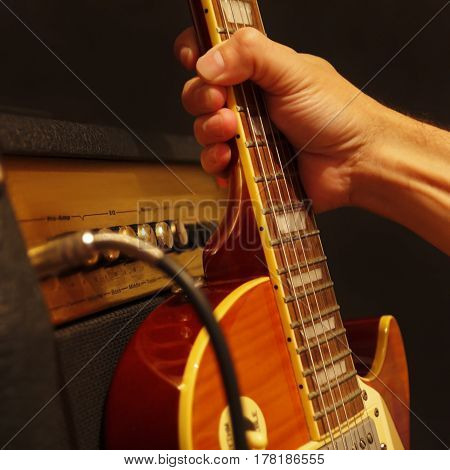 Hand takes guitar leaning against the combo amplifier on the black background. Shallow depth of field low key close up.