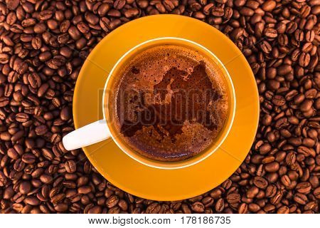 europe map on fresh espresso with a beautiful crema and strewn mediumly roasted coffee beans