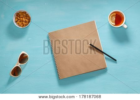 Flat composition of sketch book, pensil, sunglasses and saucer with almonds. Mockup for artists, articles, bloggers, magazines.