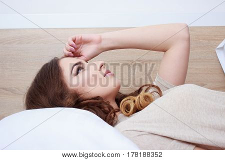 Portrait pretty young girl on bed in modern apartment