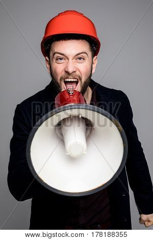 Young Engineer Is Shouting Out Over Megaphone Against Grey Background.