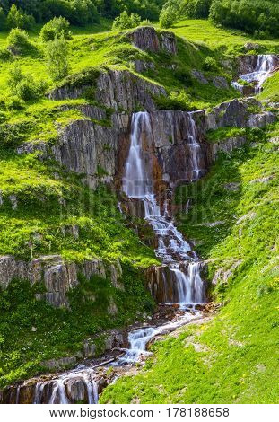 High in the mountains among the green meadows and rocks flows extremely beautiful rapid waterfall. Upper Svaneti Georgia Europe. Happy lifestyle. Beautiful universe.