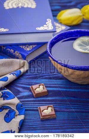Lemon tea, books, milk chokolade and yellow tulips on a blue wooden background