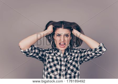 A Portrait Of A Young Very Angry Yelling Woman Touching Her Hair And Showing Teeth Against Gray Back