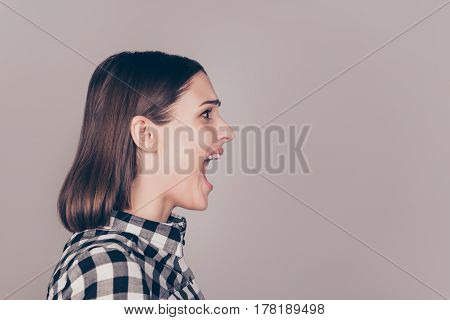 A Half-face Portrait Of A Young Disappointed Girl Screaming Against Gray Background