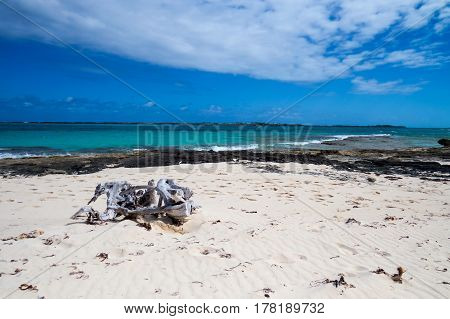 A simple tropical beach with rocks, clouds, and a piece of driftwood. New Providence Island, Nassau, Bahamas.