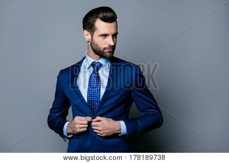 Portrait Of Serious Fashionable Handsome Man In Blue Suit And Tie Buttoning Jacket