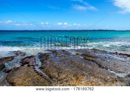 A nice rocky beach with an island, clouds, and waves. New Providence Island, Nassau, Bahamas.