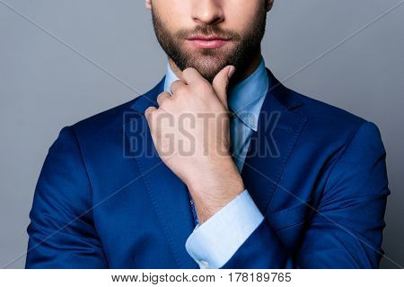 Close Up Cropped Portrait Of Serious Handsome Man In Blue Suit And Tie Touching Chin And Think
