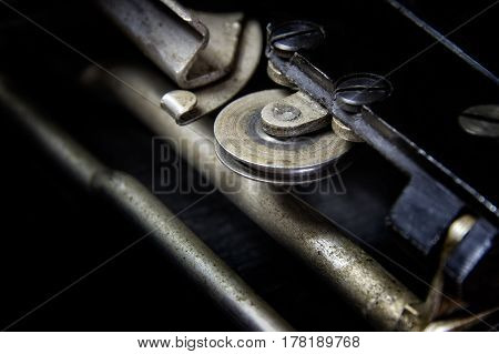 Hook & Wheel: Macro view of the sliding mechanism of a 1930's typewriter. Industrial look, large black areas, suitable for business and industrial advertising applications.
