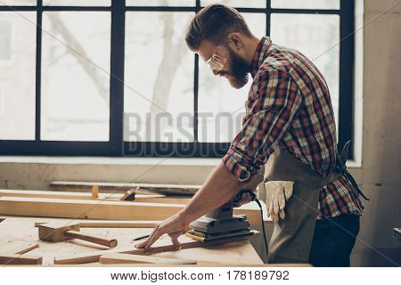 Side View Of Young Bearded Craftsman With Sander Grinding A Wooden Plank At His Workshop