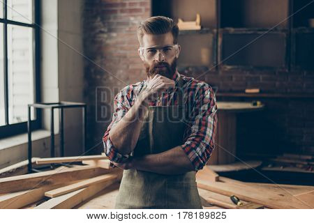 Portrait Of Brutal Handsome Concentrated Woodworker Holding His Hand On Chin While Standing At Carpe