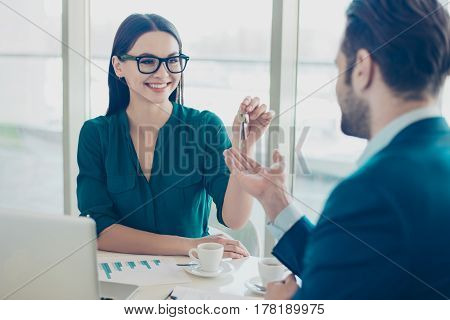 Photo Of Young Charming Pretty Woman In Glasses Giving Keys To Man In Suit
