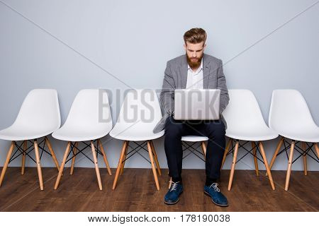 Portrait Of Young Successful Businessman Sitting On A Chair And Working With Laptop