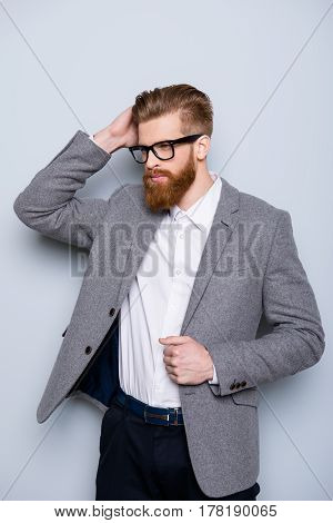 Vertical Portrait Of Young Handsome Red  Bearded Man Wearing Jacket And Glasses And Touching His Hai