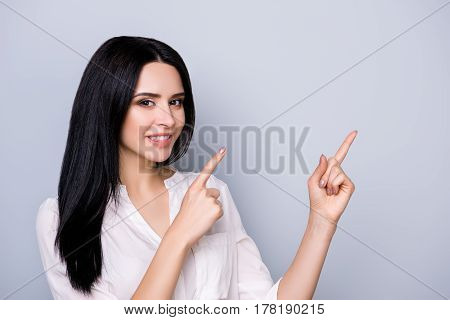 Portrait Of Beautiful Cute Smiling  Young  Woman In Formalwear With Black Hair Pointing At  Copy Spa