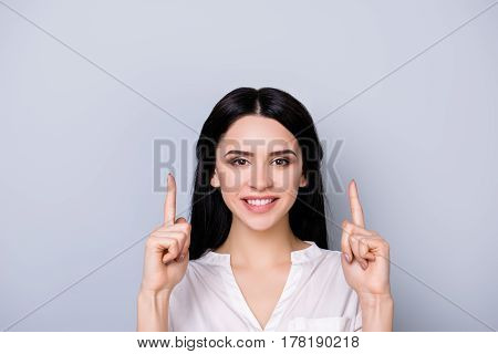 Close Up Portrait Of Beautiful Cute Smiling Young  Woman In Formalwear With Black Hair Pointing Up A