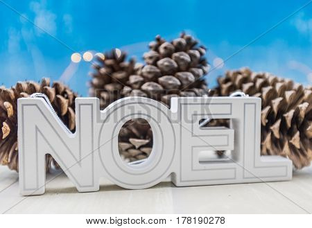 Noel Block Text Skewed With Pine Cones