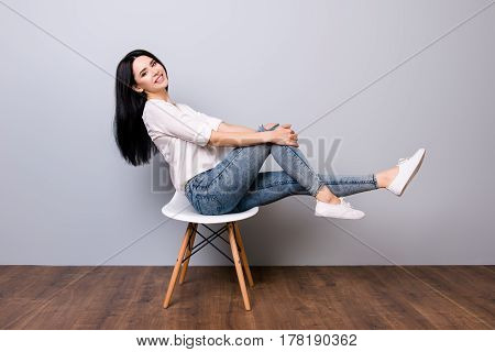 Portrait Of Young Cute Funny Woman In Jeans And White Shirt Smiling And Posing On A Chair