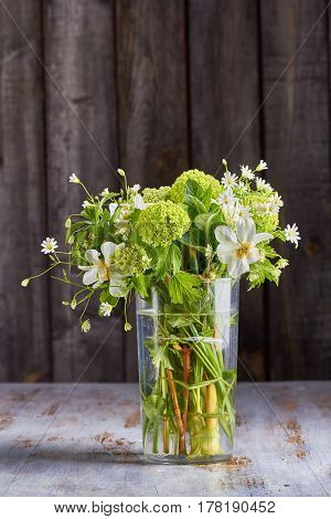 Bouquet of spring flowers in water-glass on old wooden background. Rustic style