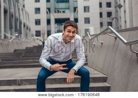 Young handsome businessman having fun near office. A young man shows a sign Victory.