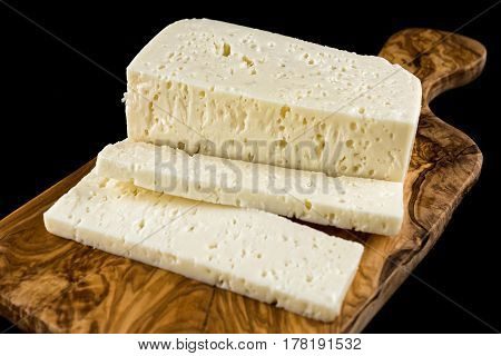 Slices of traditional sfella cheese of Peloponnese, Greece, on wooden chopping board