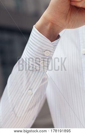Close up of a businessman's shirt cuffs. Closeup of a hand man how wears white shirt and cufflink.