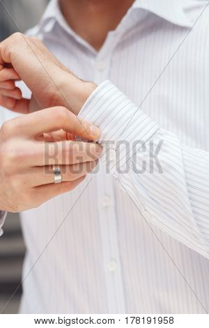 Close up of a hand businessman how wears white shirt and cufflink. Elegant white shirt with buttons.